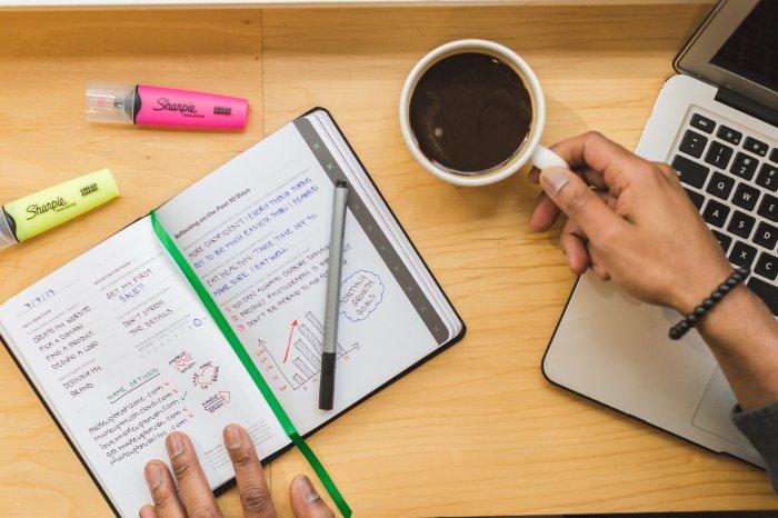 notebook next to computer hand mug